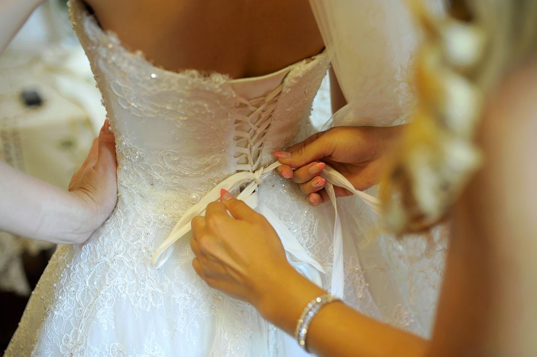 Damigella lega il corpetto di un abito da sposa