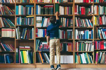 Ragazzo in punta di piedi davanti a uno scaffale di libri