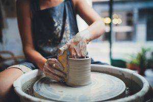 Artigiana lavora l'argilla per creare un vaso di ceramica