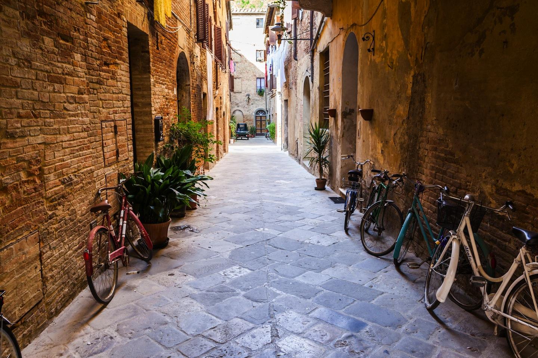 Vie di San Quirico d'Orcia con biciclette appoggiate alle pareti