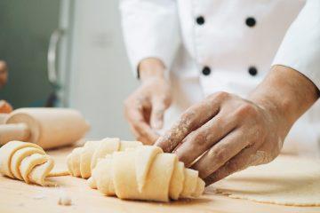 Mani di pasticcere che fanno i croissant