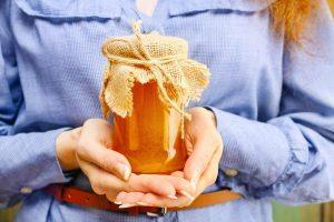 Ragazza tiene in mano un vasetto di miele toscano