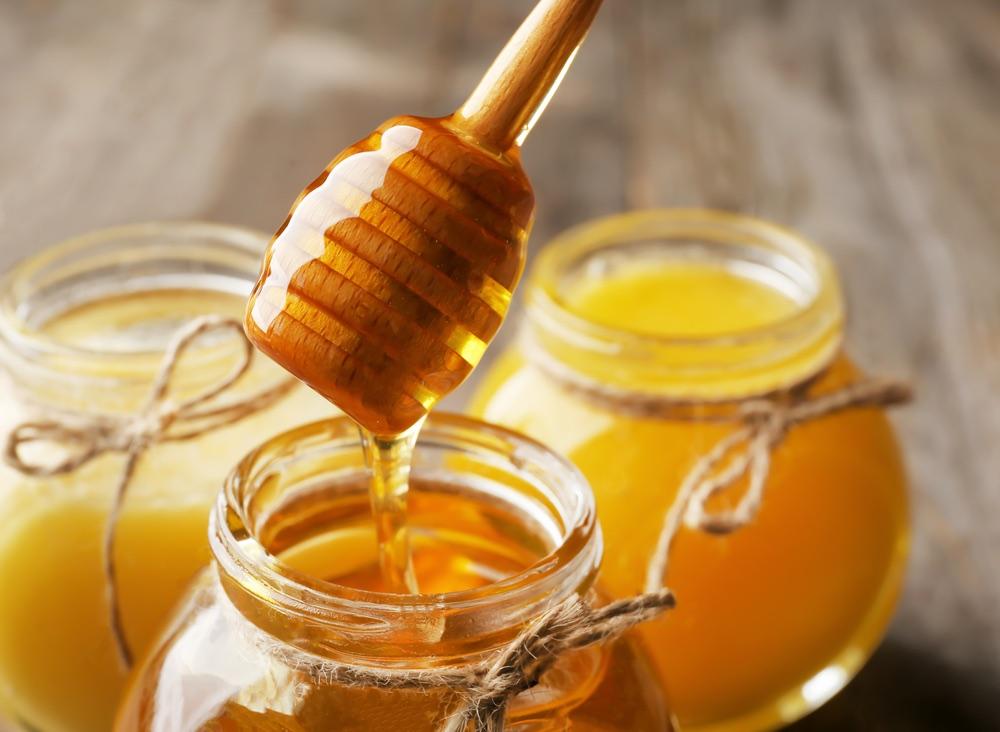 Barattoli di miele toscano su tavolo di legno