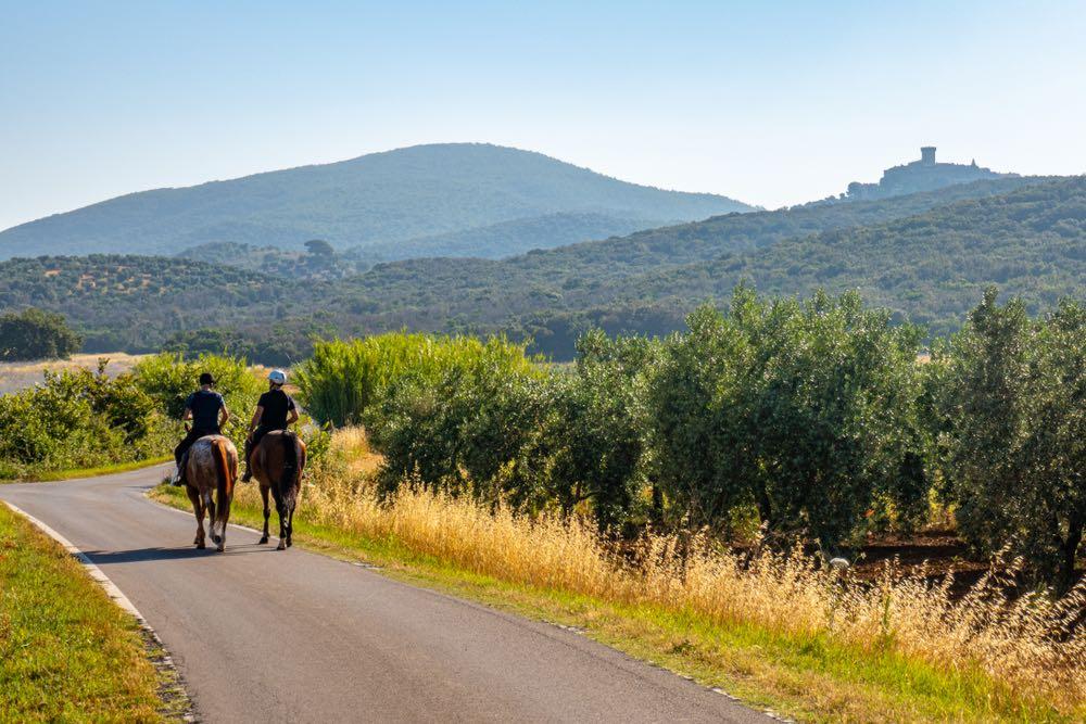 Due persone a cavallo con vista sul castello di Montauto in Toscana