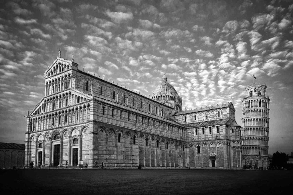 La Torre di Pisa da quasi novecento anni si staglia pendente nel cielo pisano, accanto al Duomo e al Battistero in Piazza dei Miracoli. Ma perché la Torre di Pisa pende? E quali sono i segreti nascosti nei suoi 8 piani in pendenza?