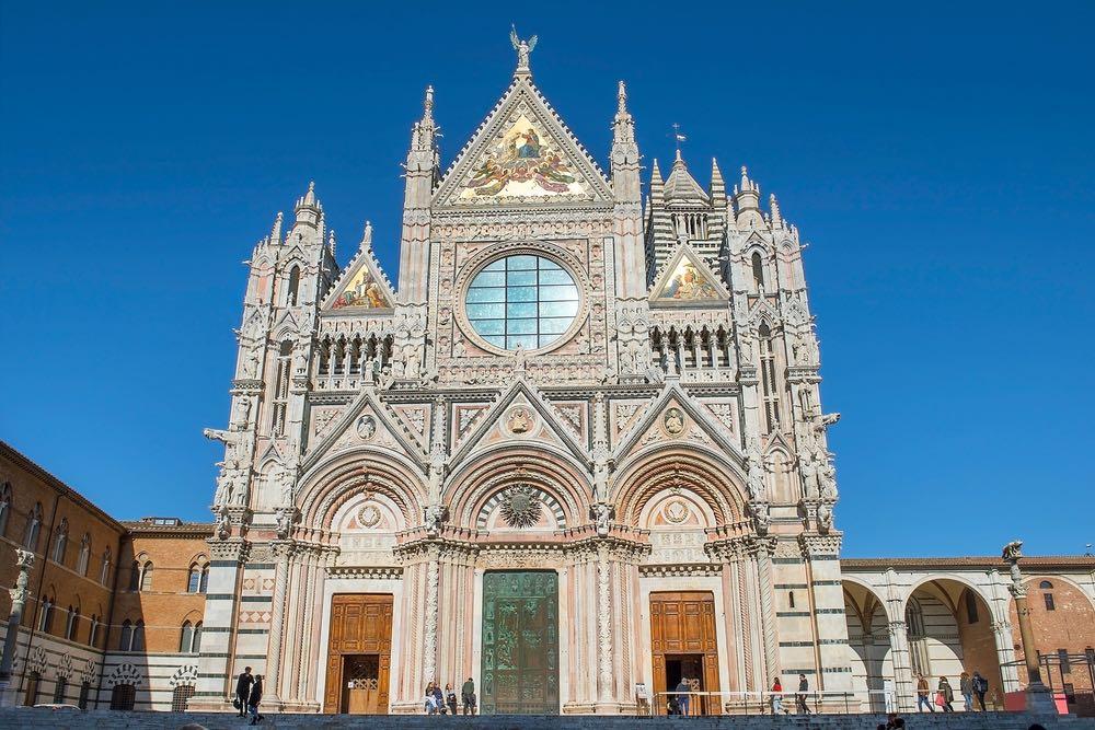 la facciata del Duomo di Siena e le due statue laterali della lupa senese