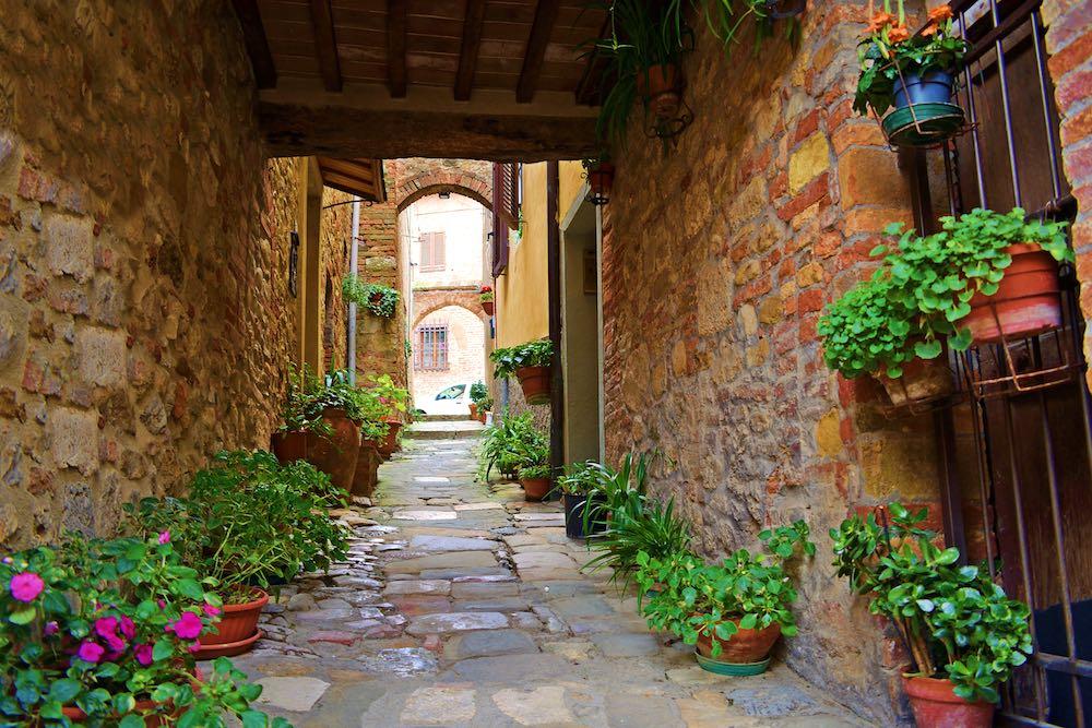 Vicolo medievale con piante di fiori a Casole d'Elsa in Toscana