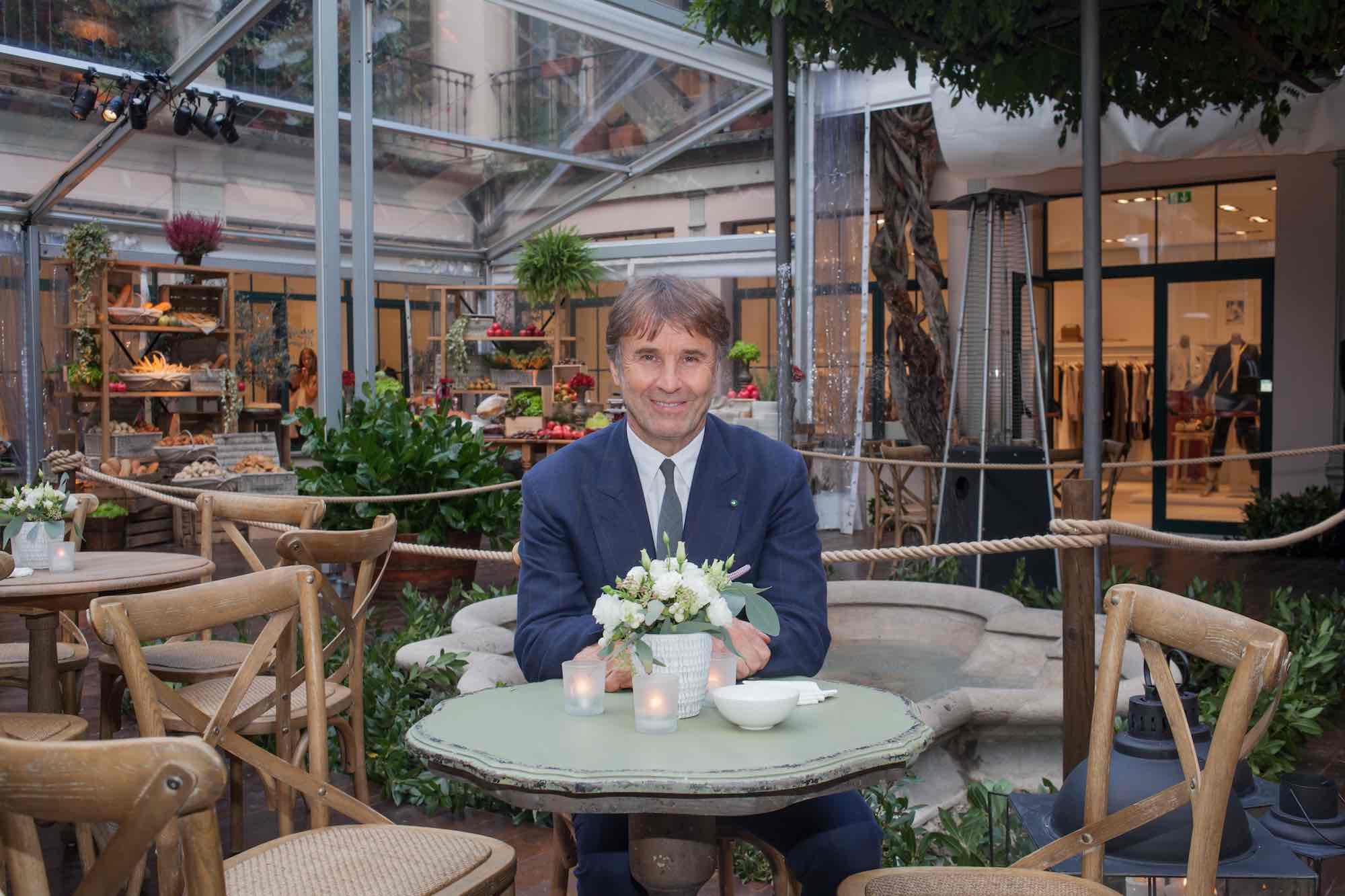 Brunello Cucinelli stilista e imprenditore dell'industria del cachemire a un tavolo con fiori davanti