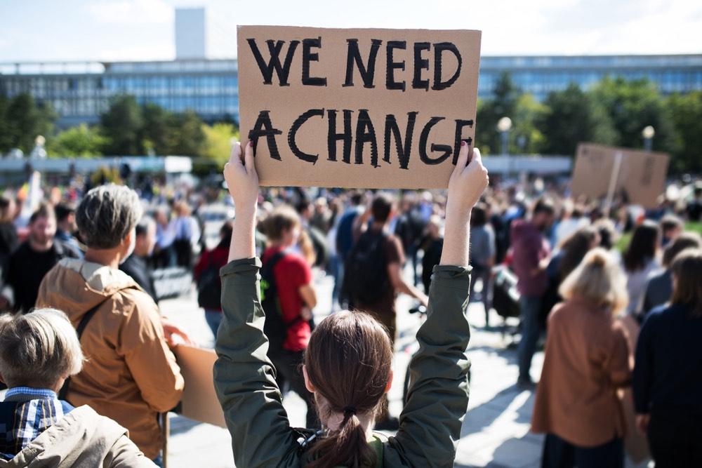 Cartello We Need a Change in manifestazione