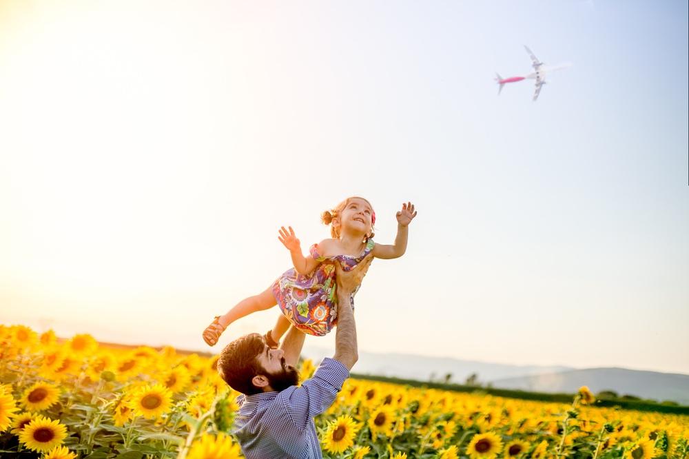 Babbo e figlia giocano in un campo di girasoli in Toscana.