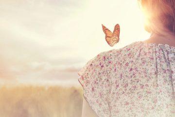Farfalla posata sulla spalla di una ragazza