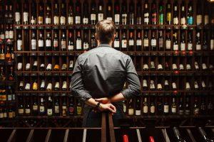 Uomo di fronte a bottiglie di vini del senese