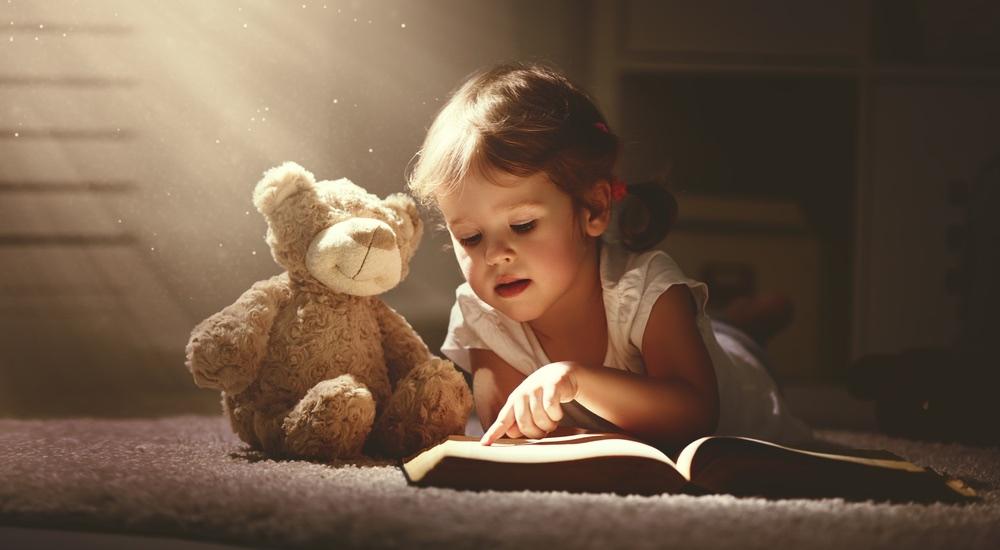 Bambina legge un libro al suo orsacchiotto