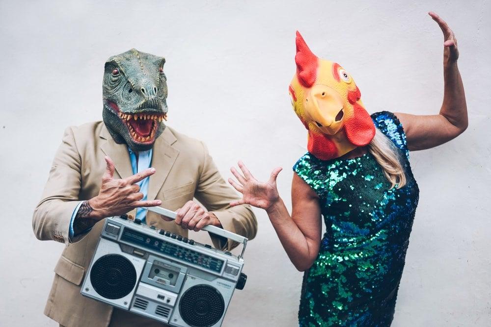 Persone divertenti che ballano con maschere in testa