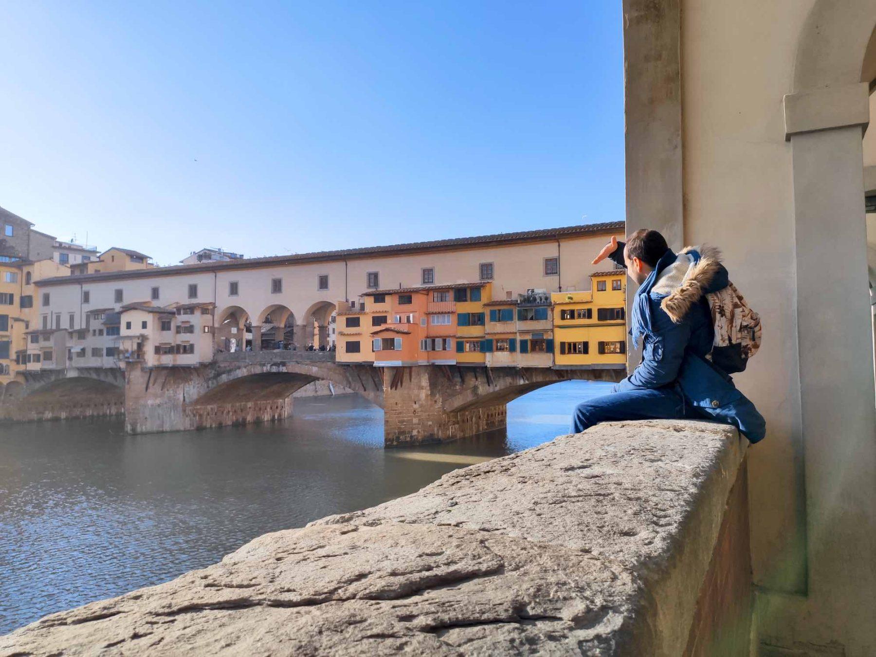Turista seduto sulla balaustra di fronte a Ponte Vecchio a Firenze
