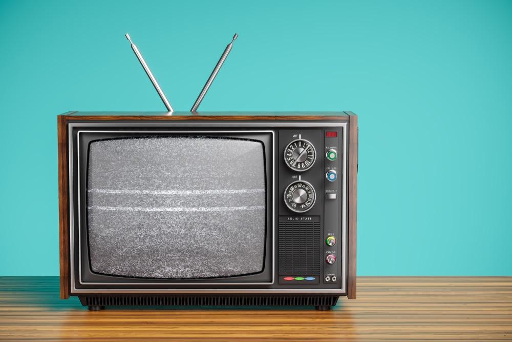 Vecchio televisore su sfondo verde acqua