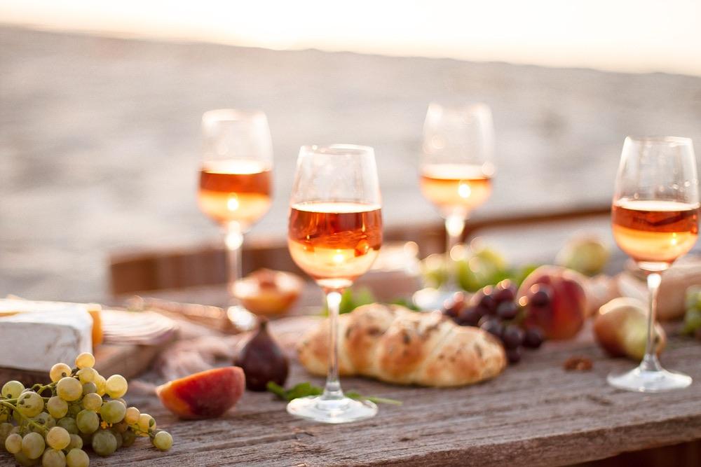 Bicchieri di vino rosè su una tavola al mare per una cena di pesce