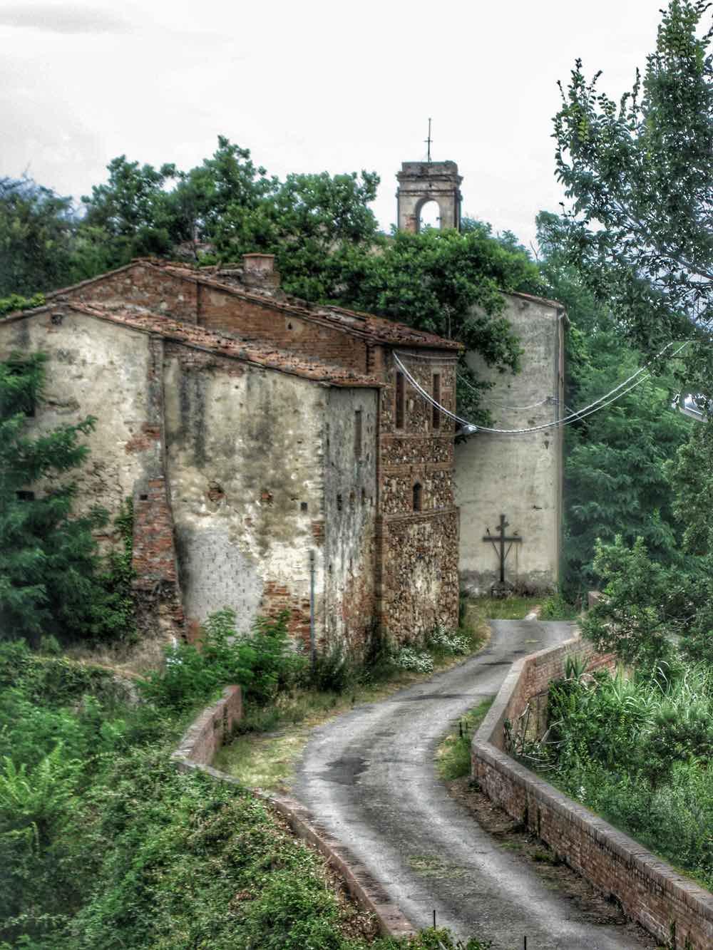 Strada tra case abbandonate a Brento Sanico in Toscana