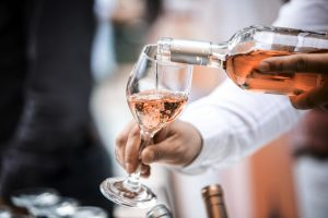 Sommelier mesce in un bicchiere vino rato toscano