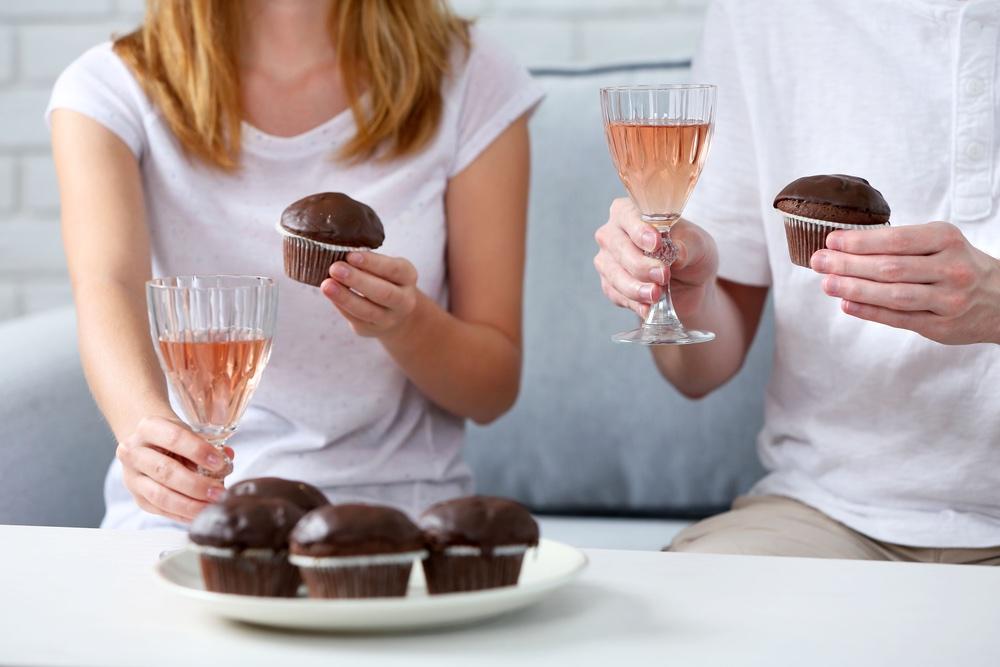 Due persone tengono in mano bicchieri di vino rosato assaggiando dei muffin