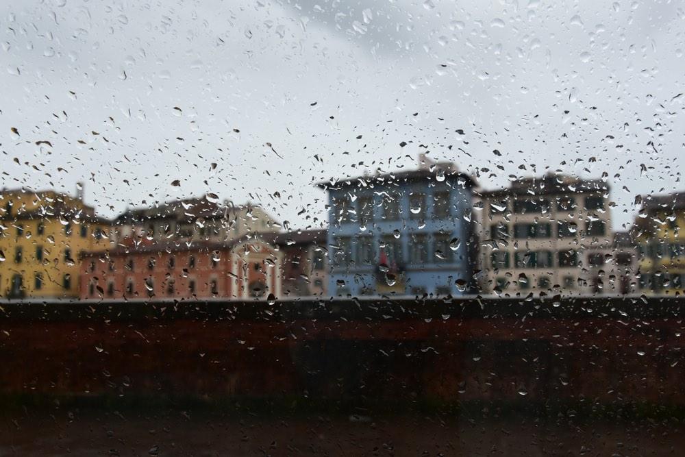 I lungarni di Pisa in una giornata di pioggia fotografati da dietro un vetro