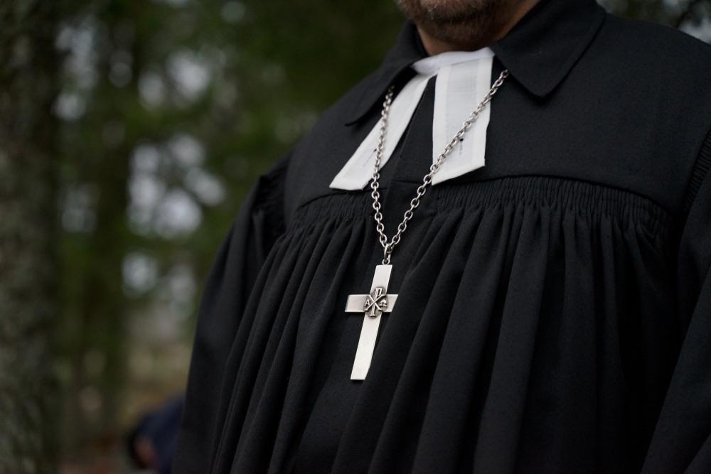 Croce d'argento aòl collo di un prete nel bosco