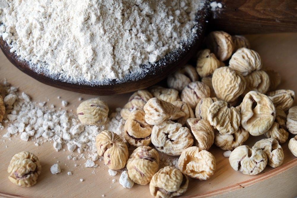 Farina di castagne in una ciotola di legno con castagne sul tavolo