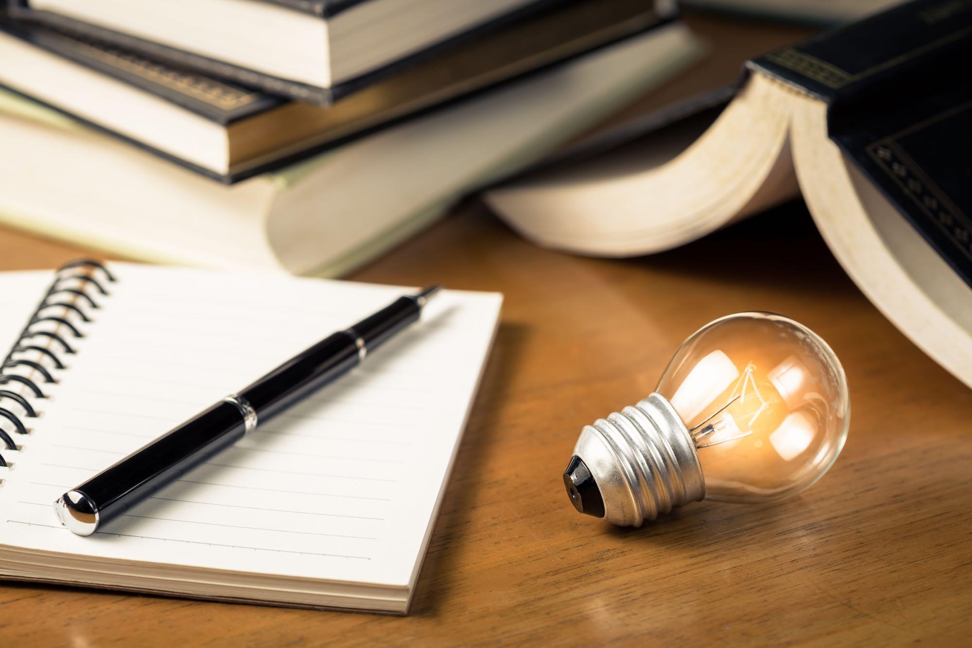 Lampadina su tavolo con quaderno e penna