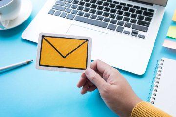 Il concetto di email marketing: mano che tiene busta da lettere gialla con pc sullo sfondo