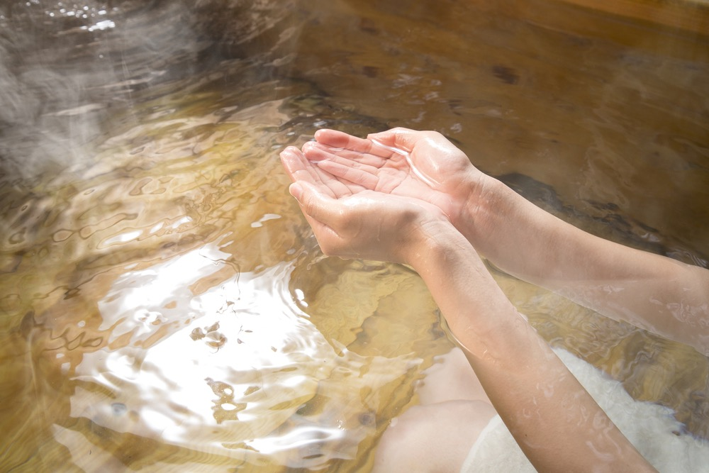 Mani che raccolgono acqua termale trasparente