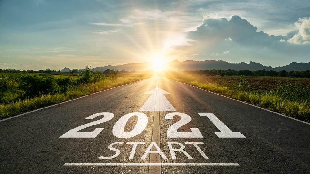 Scritta 2021 su strada con sole all'orizzonte