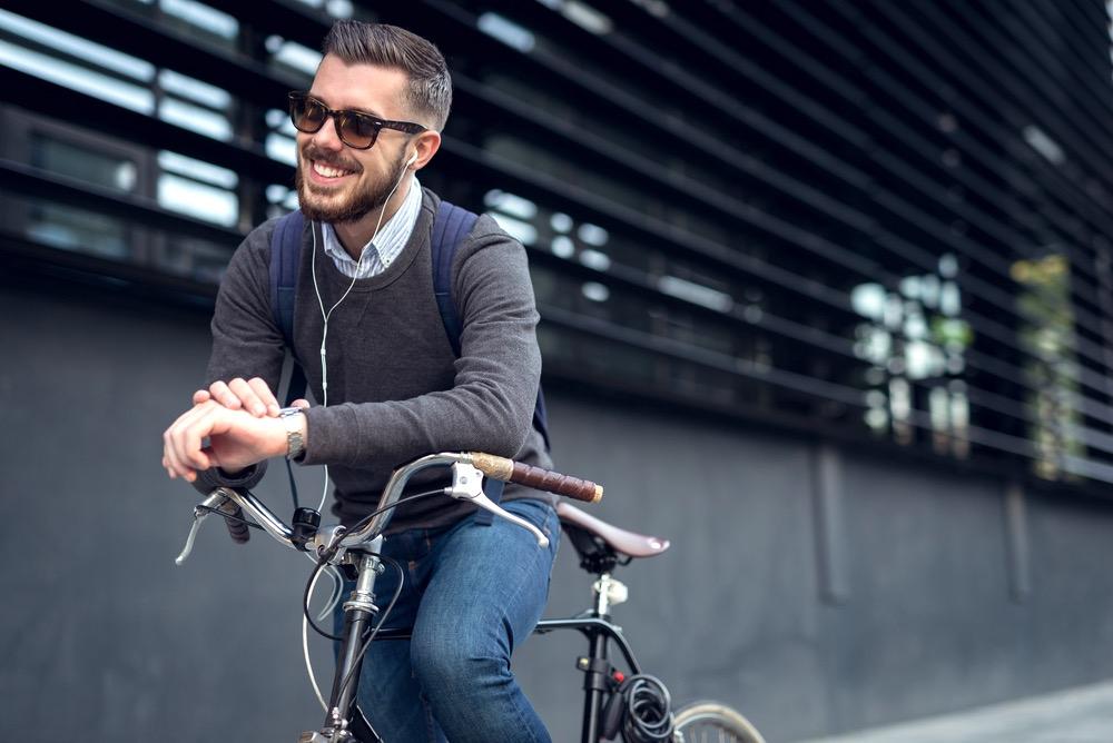 Ragazzo sorride appoggiato a una bicicletta in città