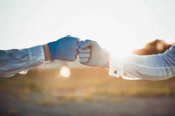 Mani con guanti che si toccano in segno di solidarietà