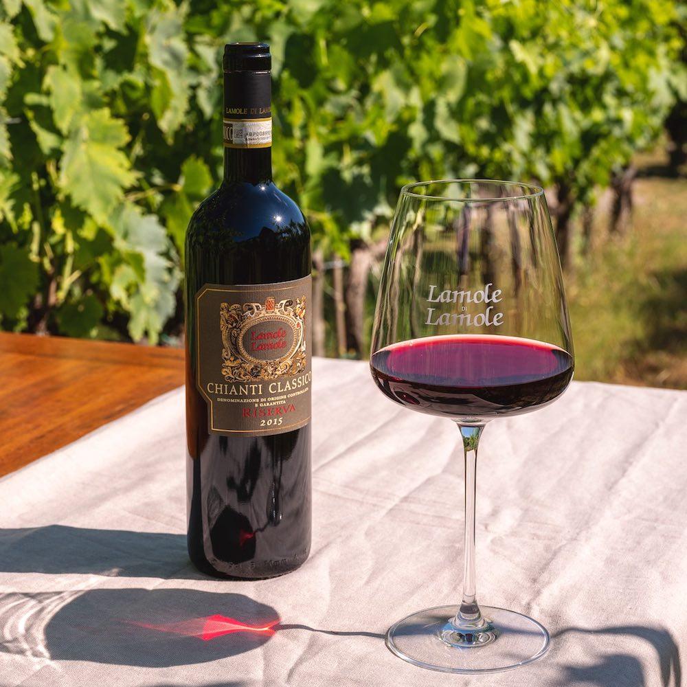 Bicchiere di vino rosso con bottiglia di Lamole di Lamole Chianti Classico