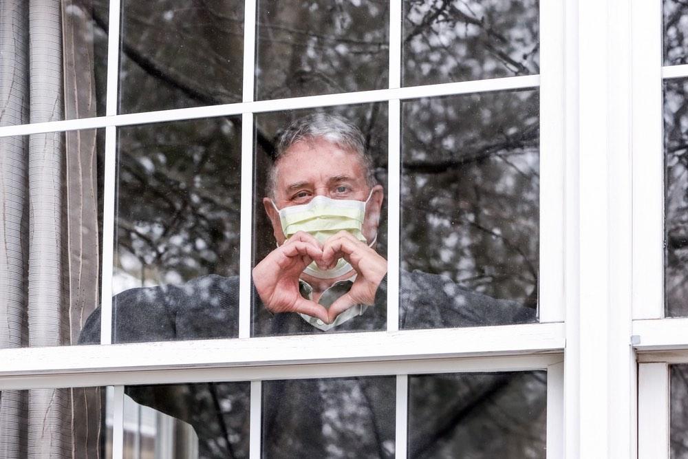 Signore alla finestra con mascherina e mani a cuore