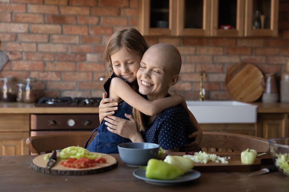Mamma e figlia si abbracciano davanti a una tavola imbandita