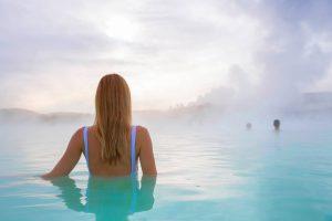Ragazza con costume intero blu in una piscina termale