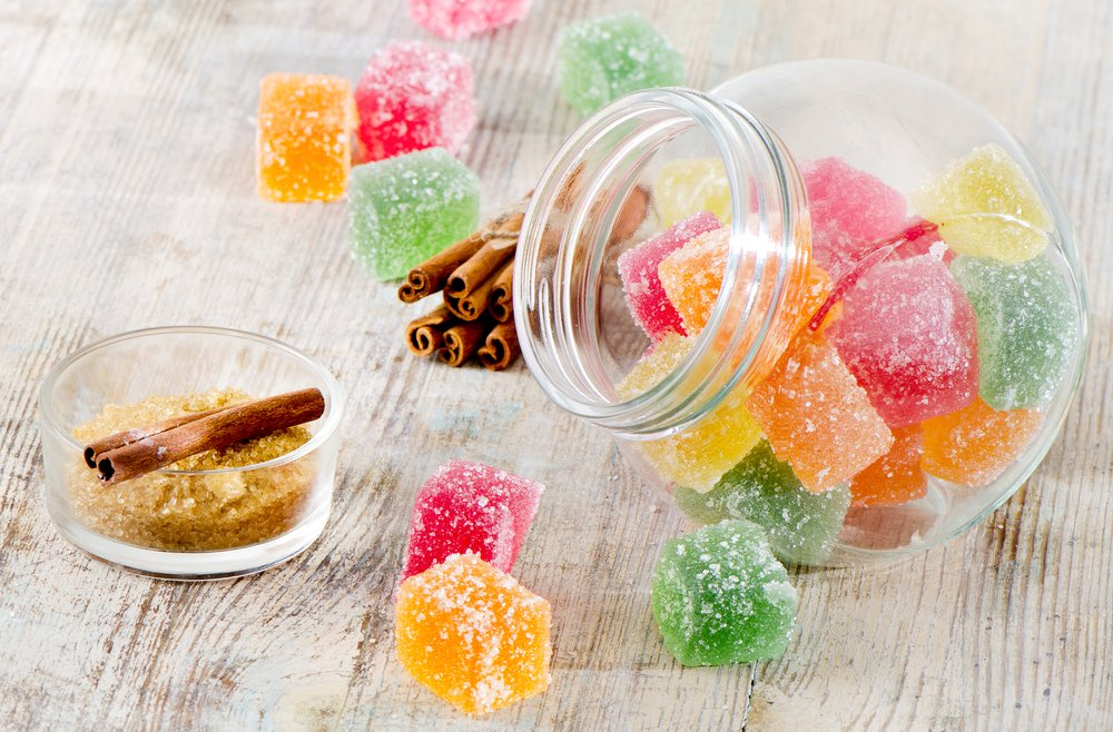 Caramelle colorate alla frutta in un vasetto di vetro su un tavolo di legno