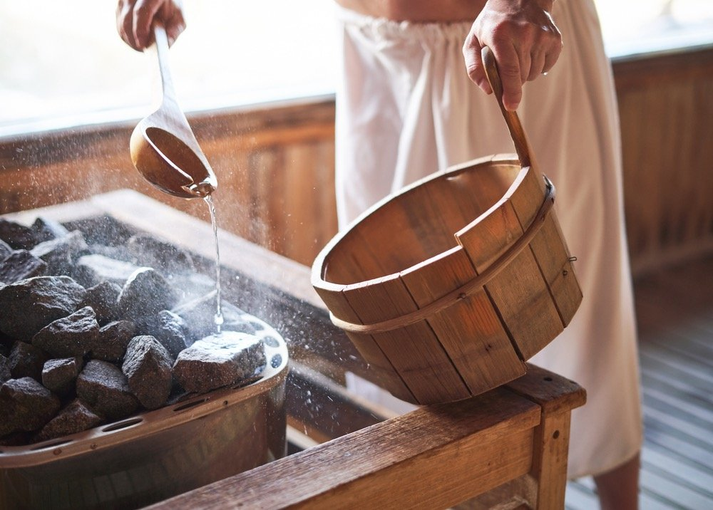 Un uomo getta acqua sulle rocce calde nella sauna alle Terme di Gambassi