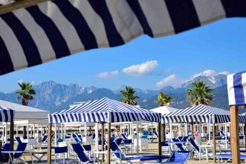Alpi Apuane vista da uno stabilimento in Versilia con ombrelloni bianchi e blu