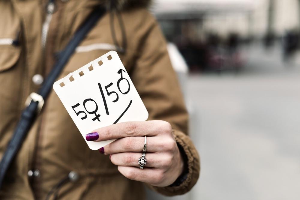 Ragazza con smalto viola tien in mano cartello sull'uguaglianza di genere