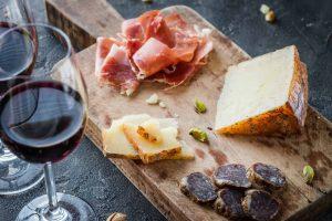 Antipasto toscano di salumi e formaggio con calice di vino rosso