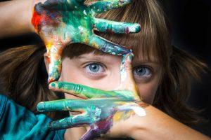 Bambina con occhi azzurri guarda attraverso le sue mani colorate con le tempere