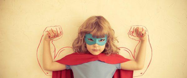 Bambina vestita da supereroe con maschera azzurra e mantello rosso