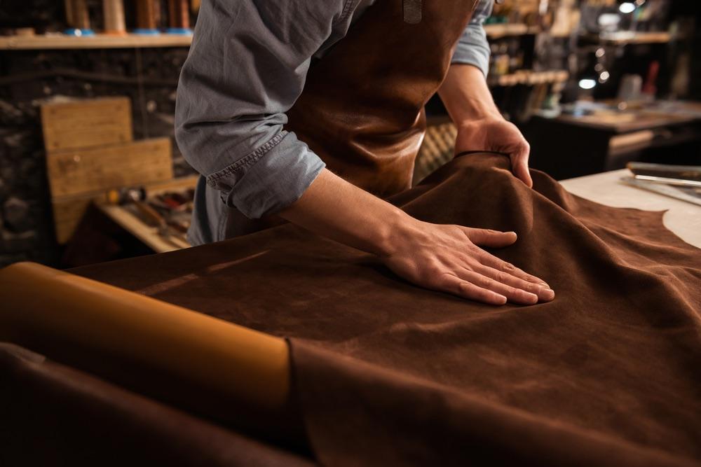 Mani di un artigiano che sceglie la pelle per le scarpe