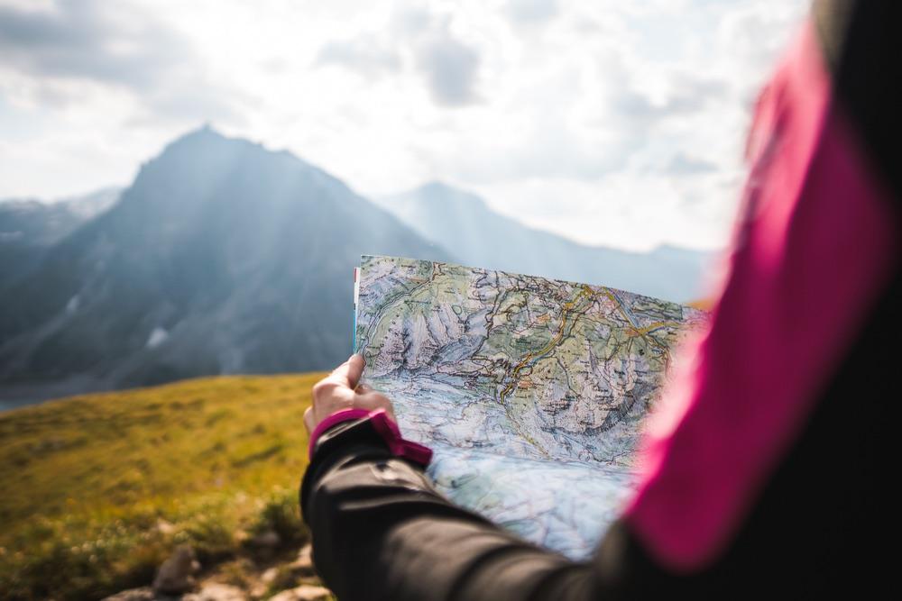 Ragazza con mappa in mano davanti a panorama di montagne