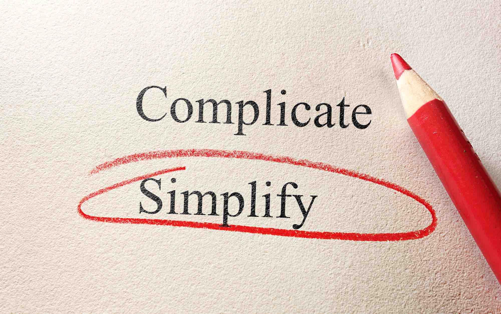 Una matita rossa su foglio bianco che ha selezionato la parola semplicità rispetto a complicato