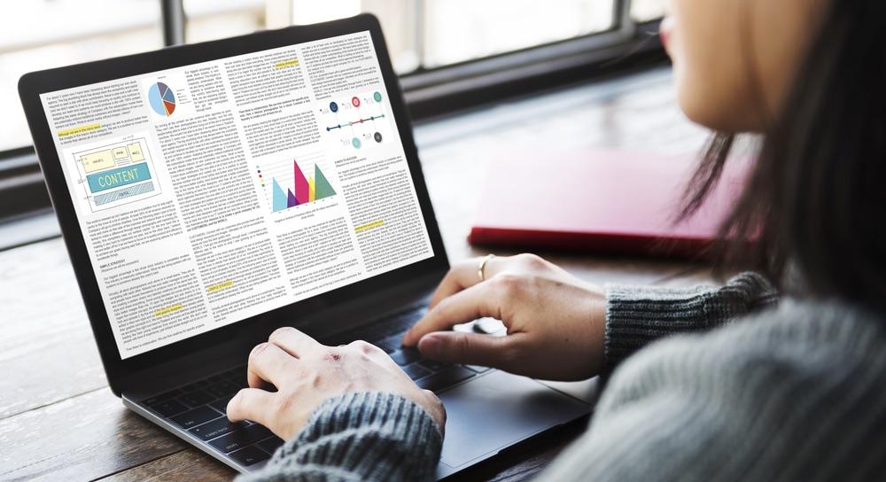 Ragazza scrive articolo con grafici su computer