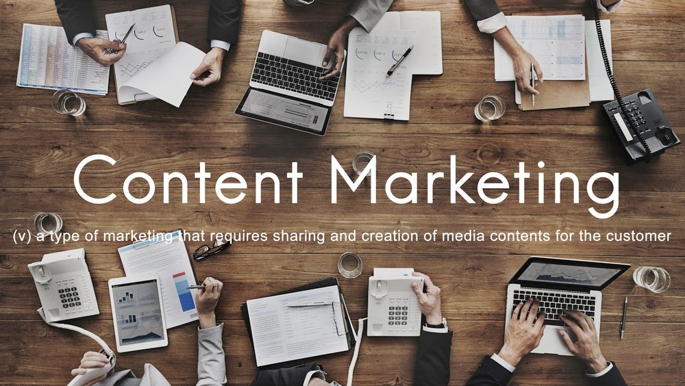 Persone lavorano con un computer su tavolo di legno con scritta Content Marketing