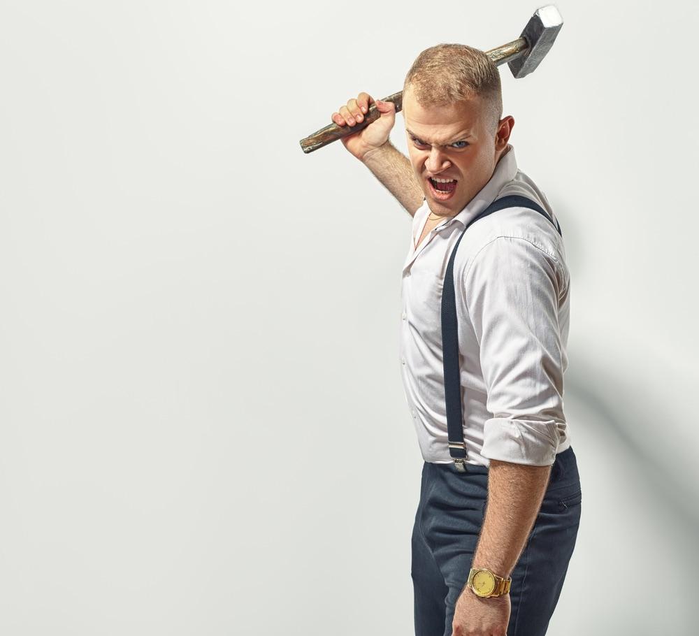 Ragazzo arrabbiato con martello in mano pronto a rompere qualcosa